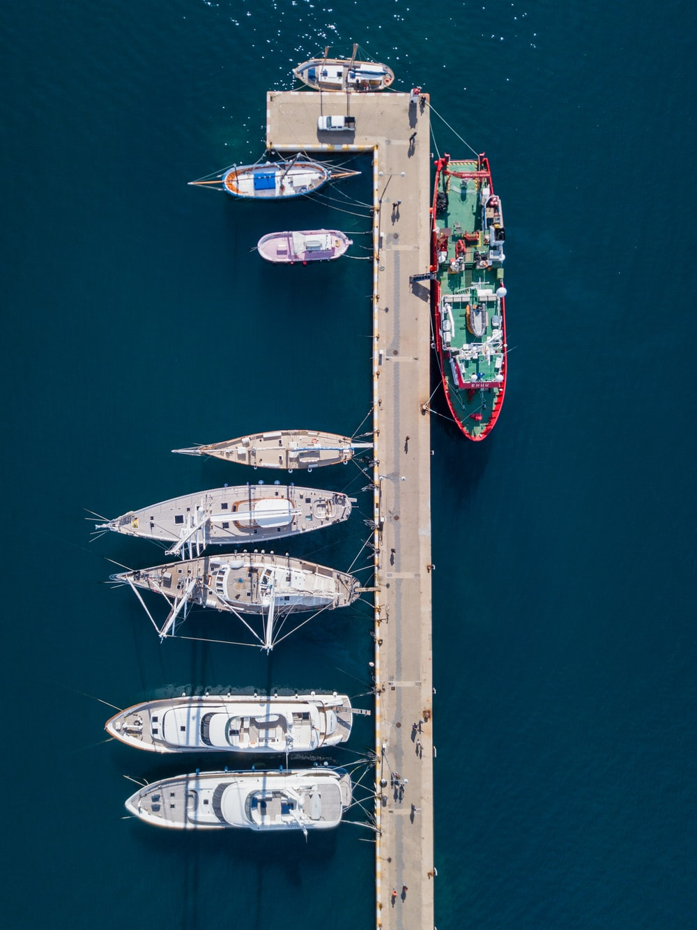 aerial photography of white and red boats near gray dock at daytime