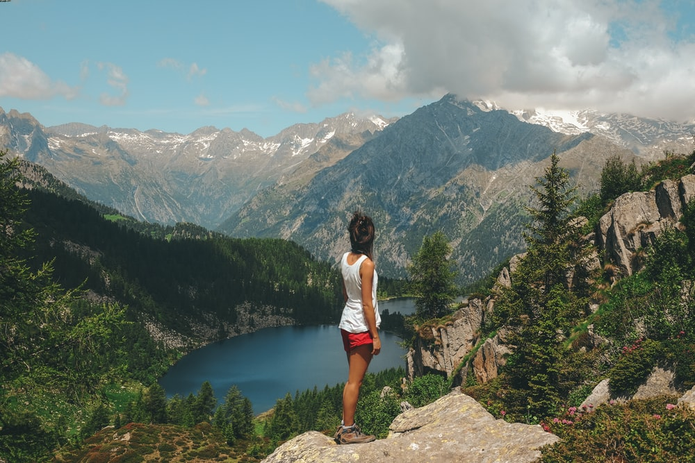 woman standing on rock on top of mountain