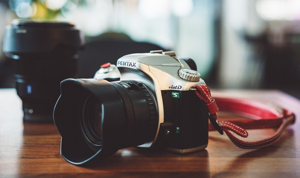 black and gray Pentax DSLR camera on wooden table beside zoom lens