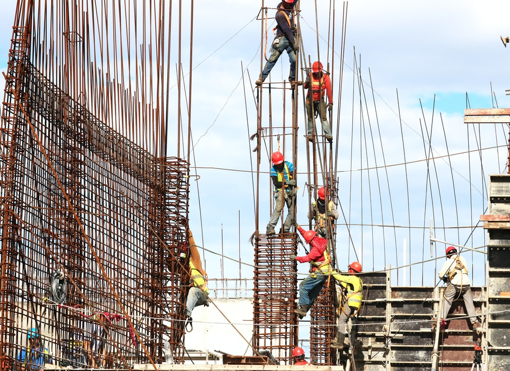 people working on building during daytime