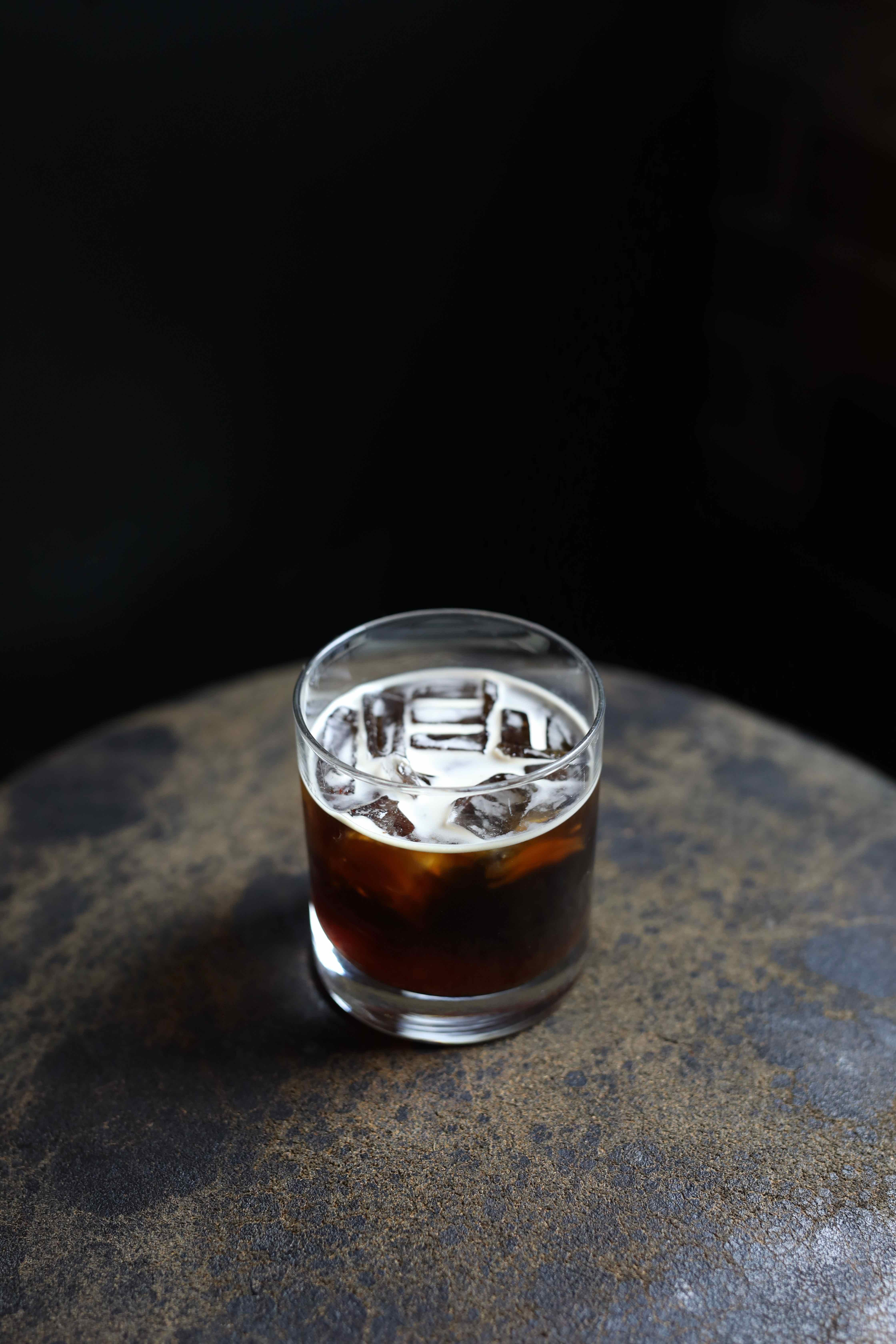 glass of iced coffee placed on brown stone
