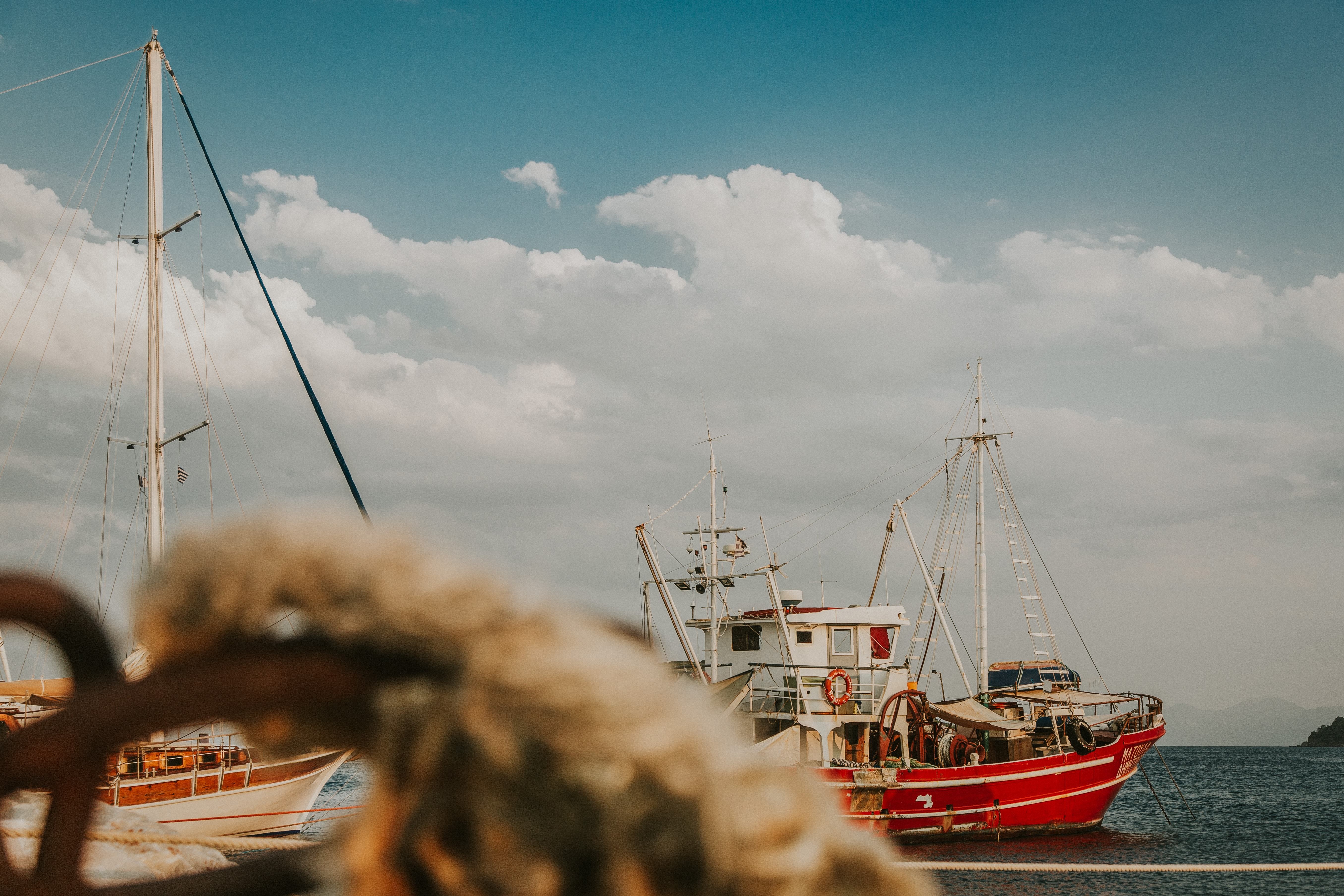 red and white fishing vessel on sea under cloudy sky