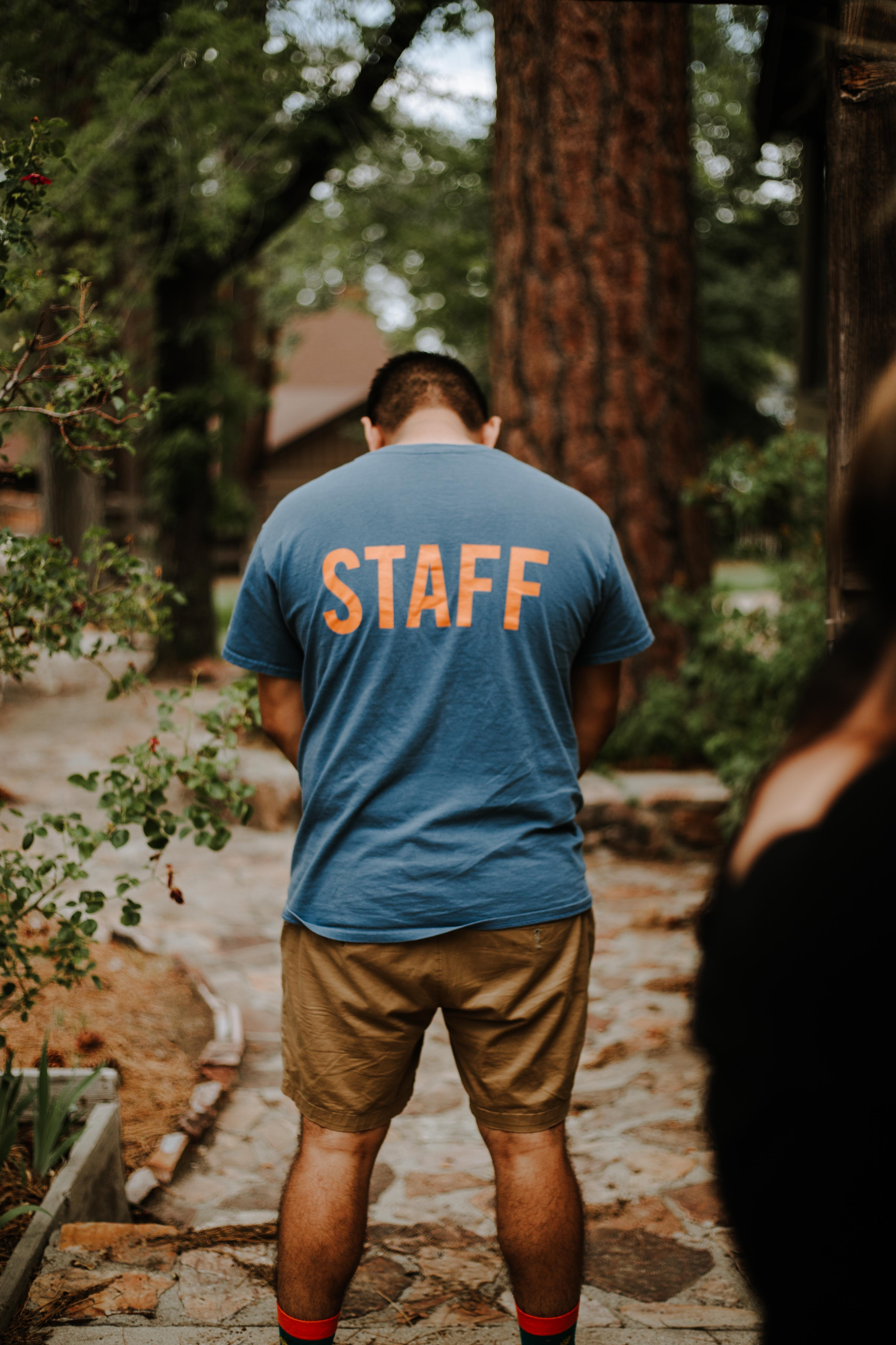 standing man wearing staff t-shirt near tree