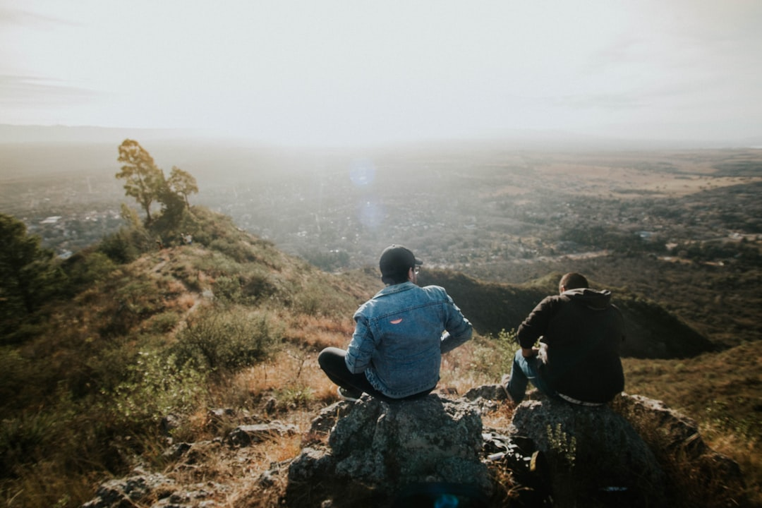 two person sitting on rock