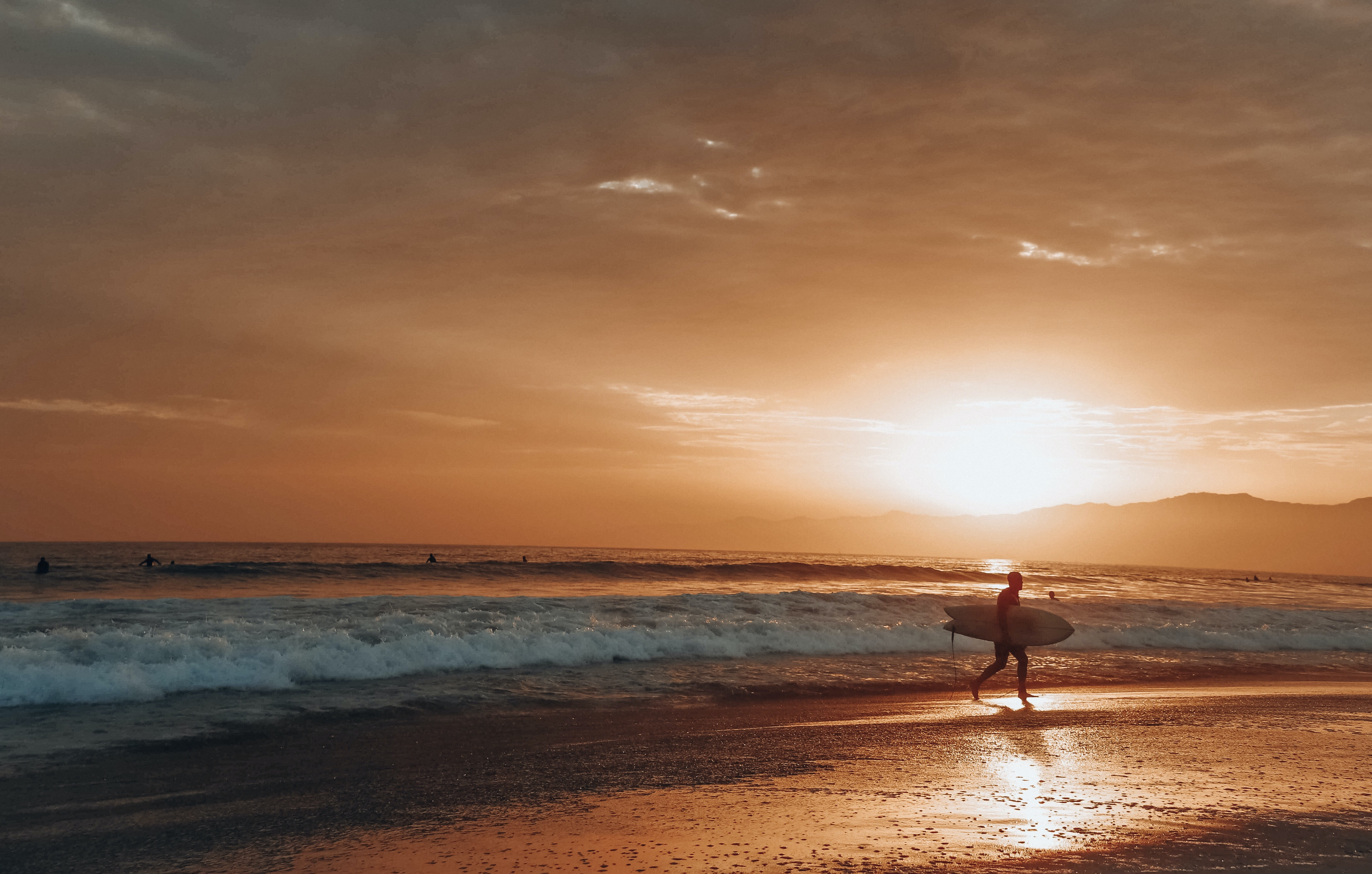 man carrying surfboard at the beach