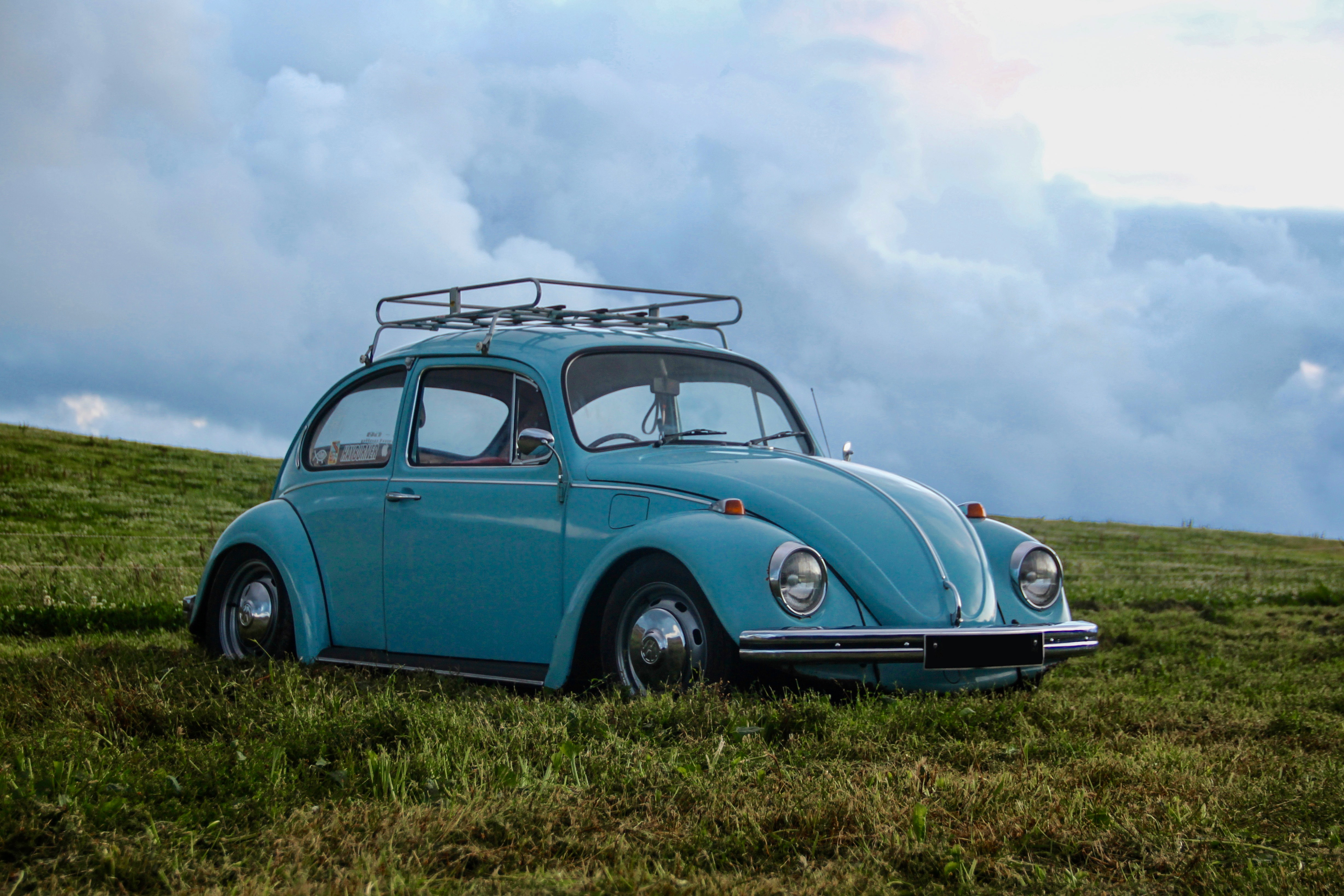blue Volkswagen Beetle on grass field