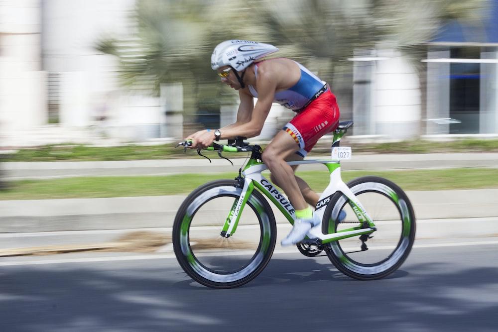 man riding on road bicycle during daytime