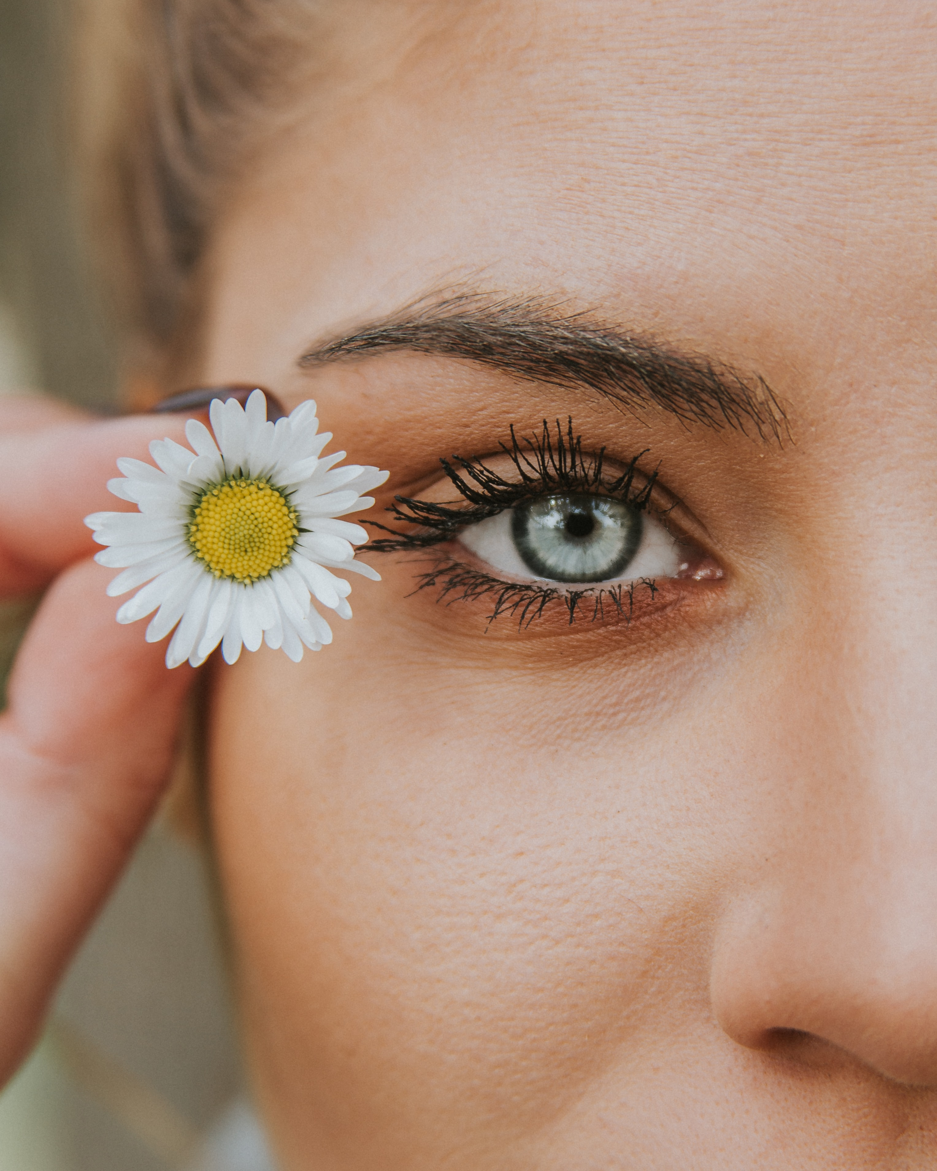 white petaled flower near woman eye