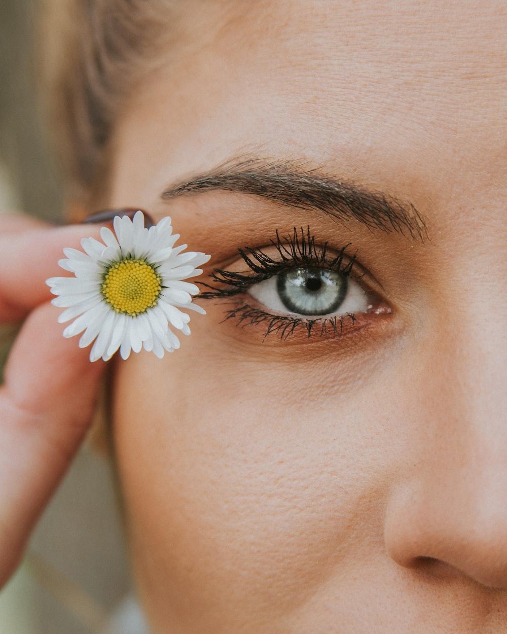 white petaled flower near woman eye