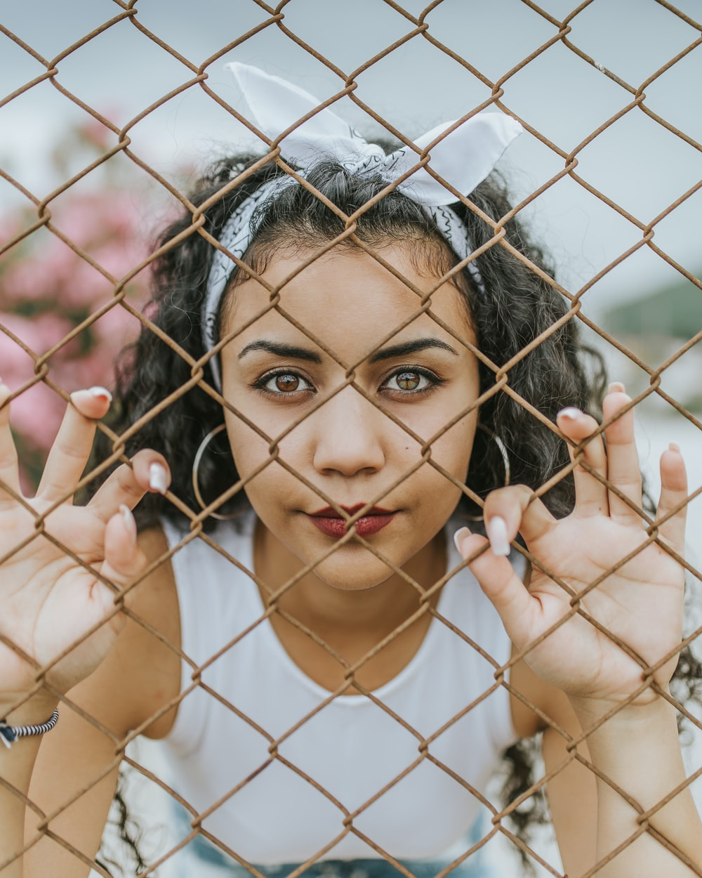 woman holding chain link fence