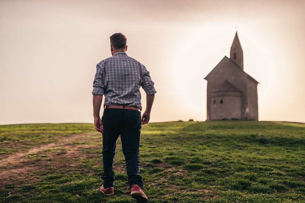 man walking in green grass