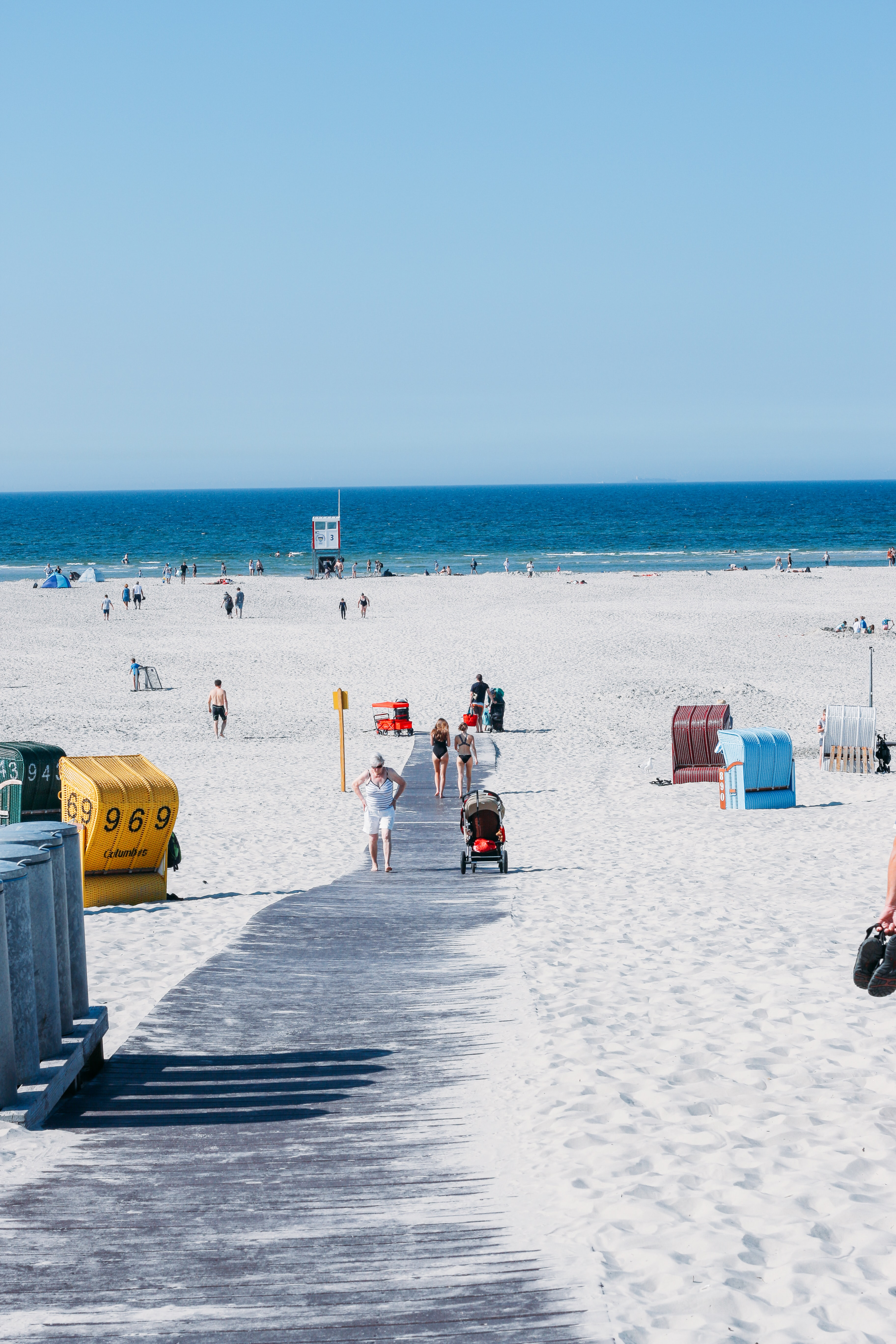aerial photography of people walking along beach