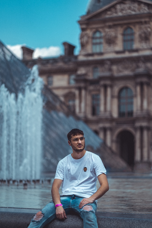 man sitting beside fountain