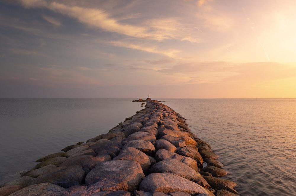 scenery of gray rocks pier on body of water during daytine
