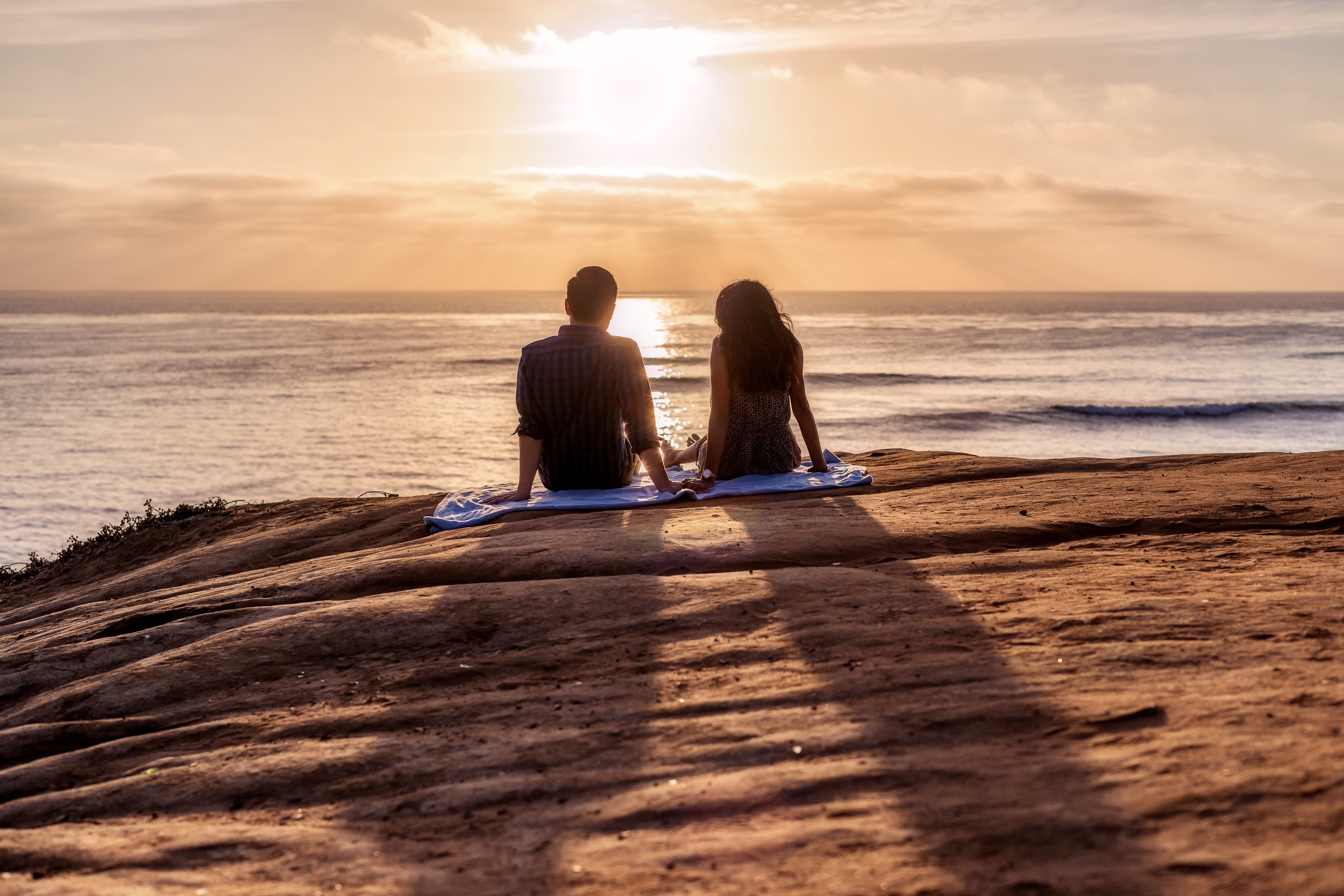 man and woman sitting on rock facing sea during golden hour