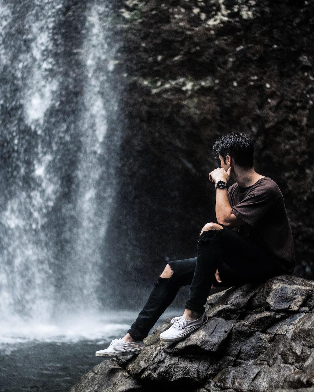 man sitting near waterfalls
