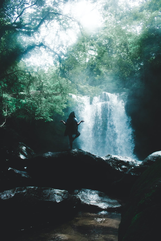 woman facing waterfall doing yoga