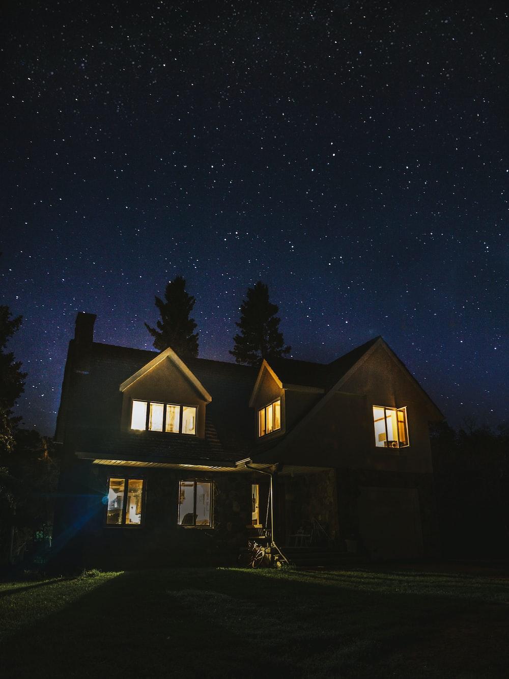 lighted 2-storey house near trees