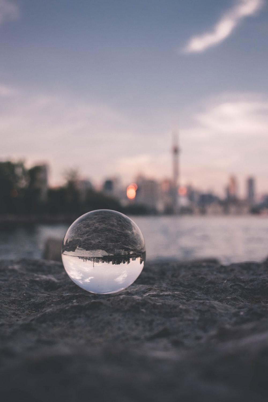 selective focus photography of glass ball on sandy ground