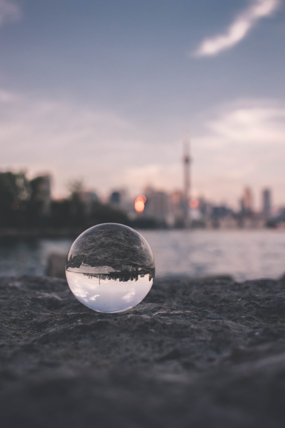 selective focus photography of glass ball on sandy ground
