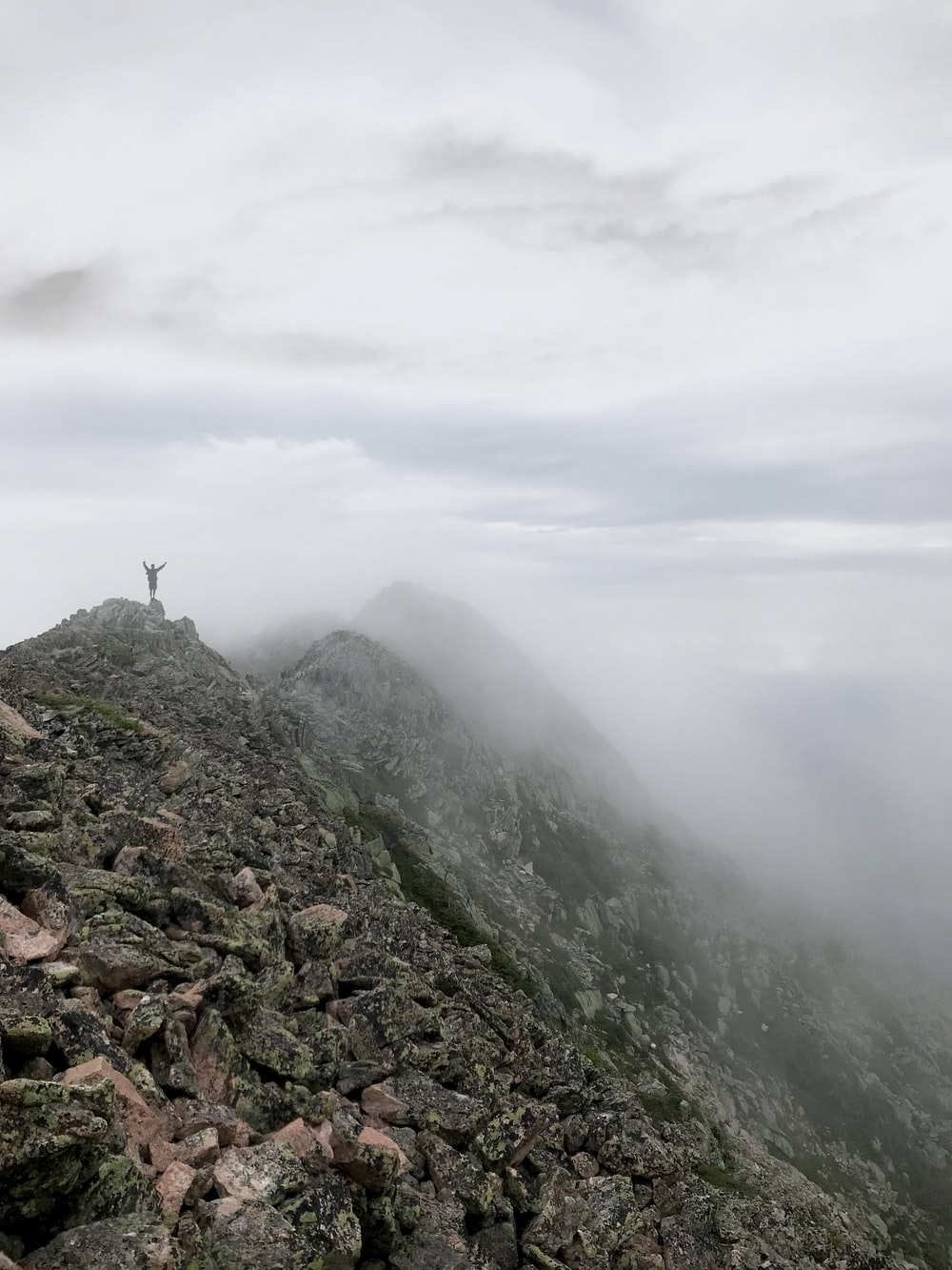 person standing on mountain summit with fog