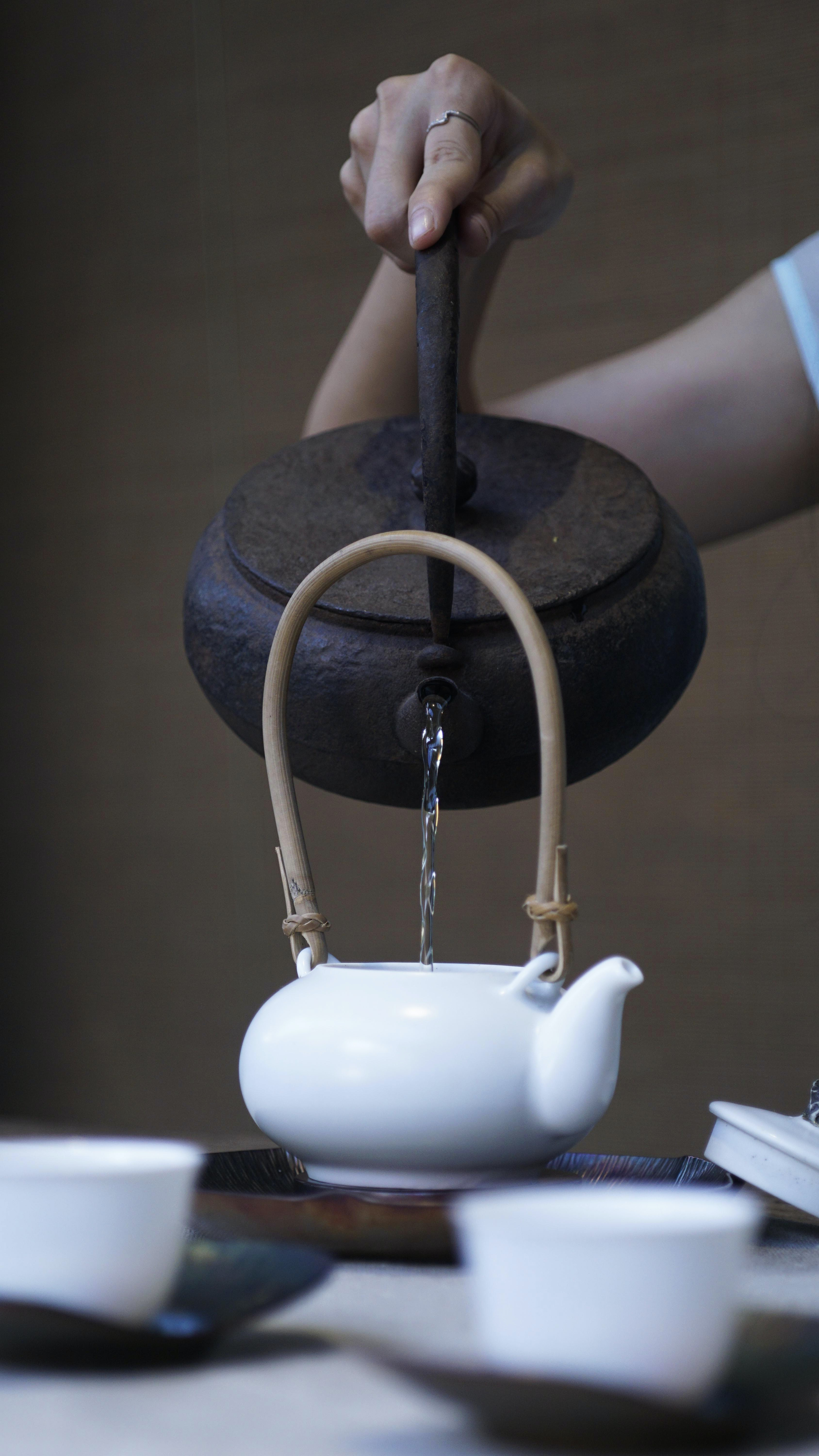 person pouring water on ceramic teapot