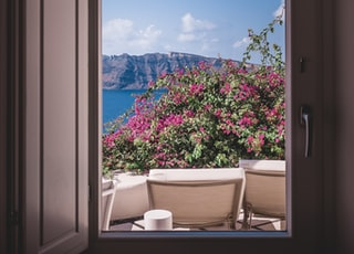 opened window showing outdoor lounger and pink flowers with mountain background