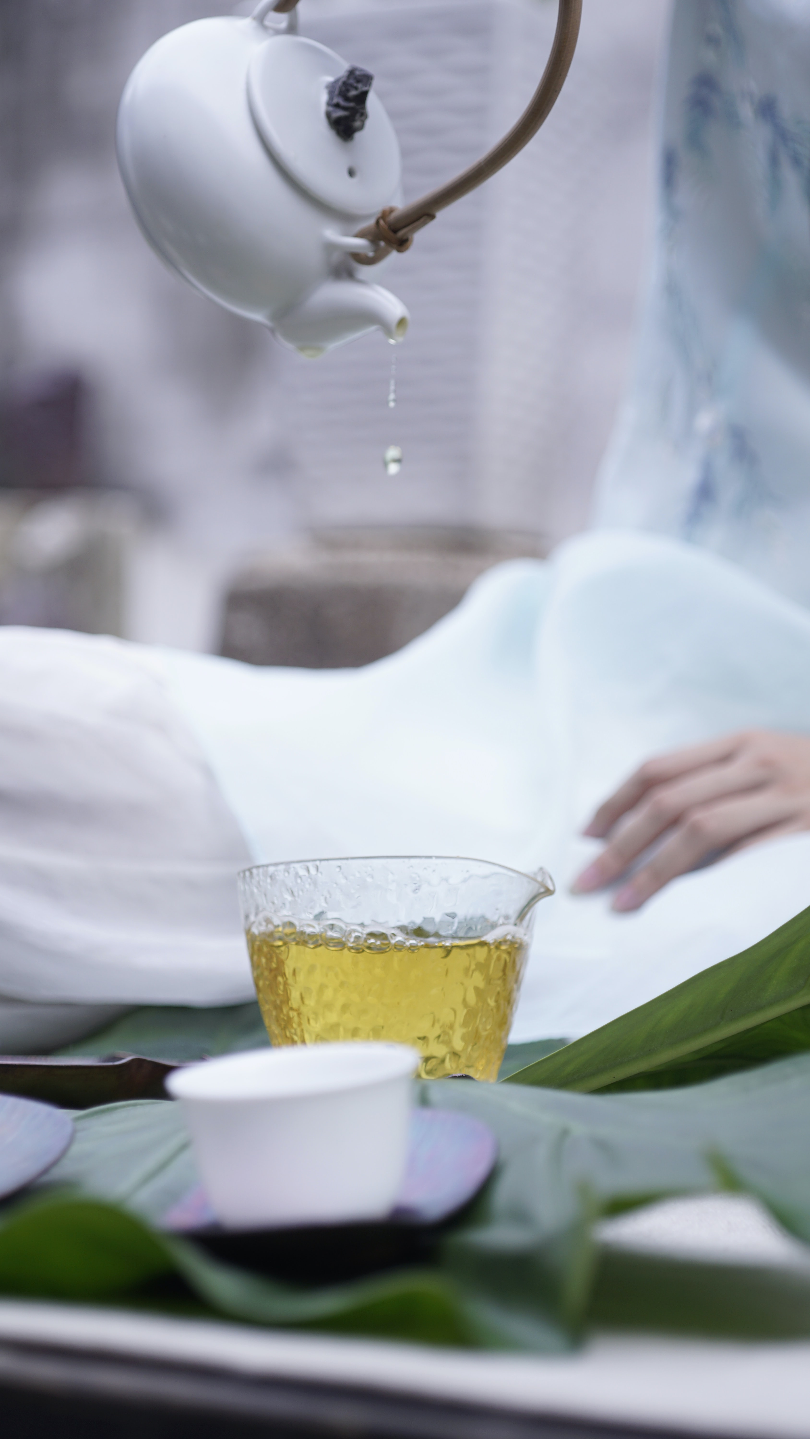 person pouring tea on glass cup