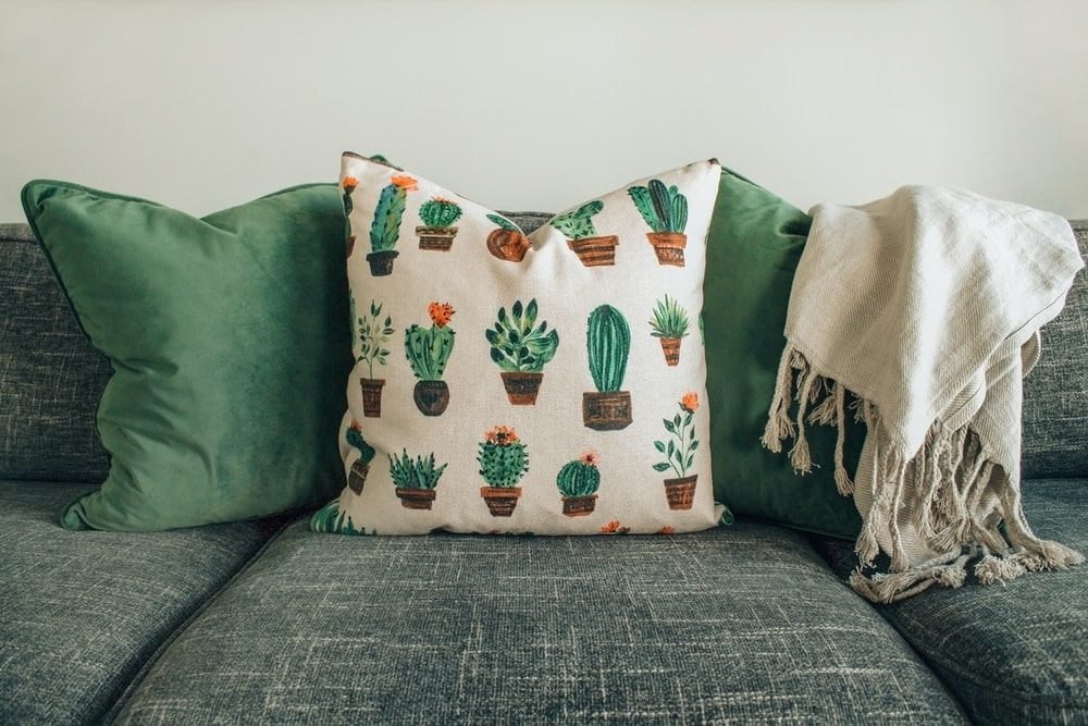three throw pillows and one white fringed blanket placed on top of gray sofa