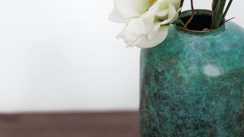 white petaled flower in green ceramic vase