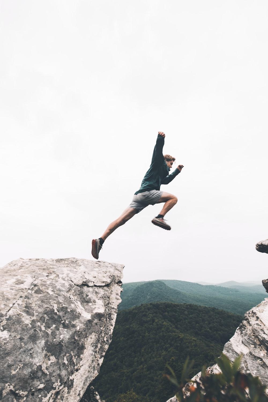 man jumping above rock mountain