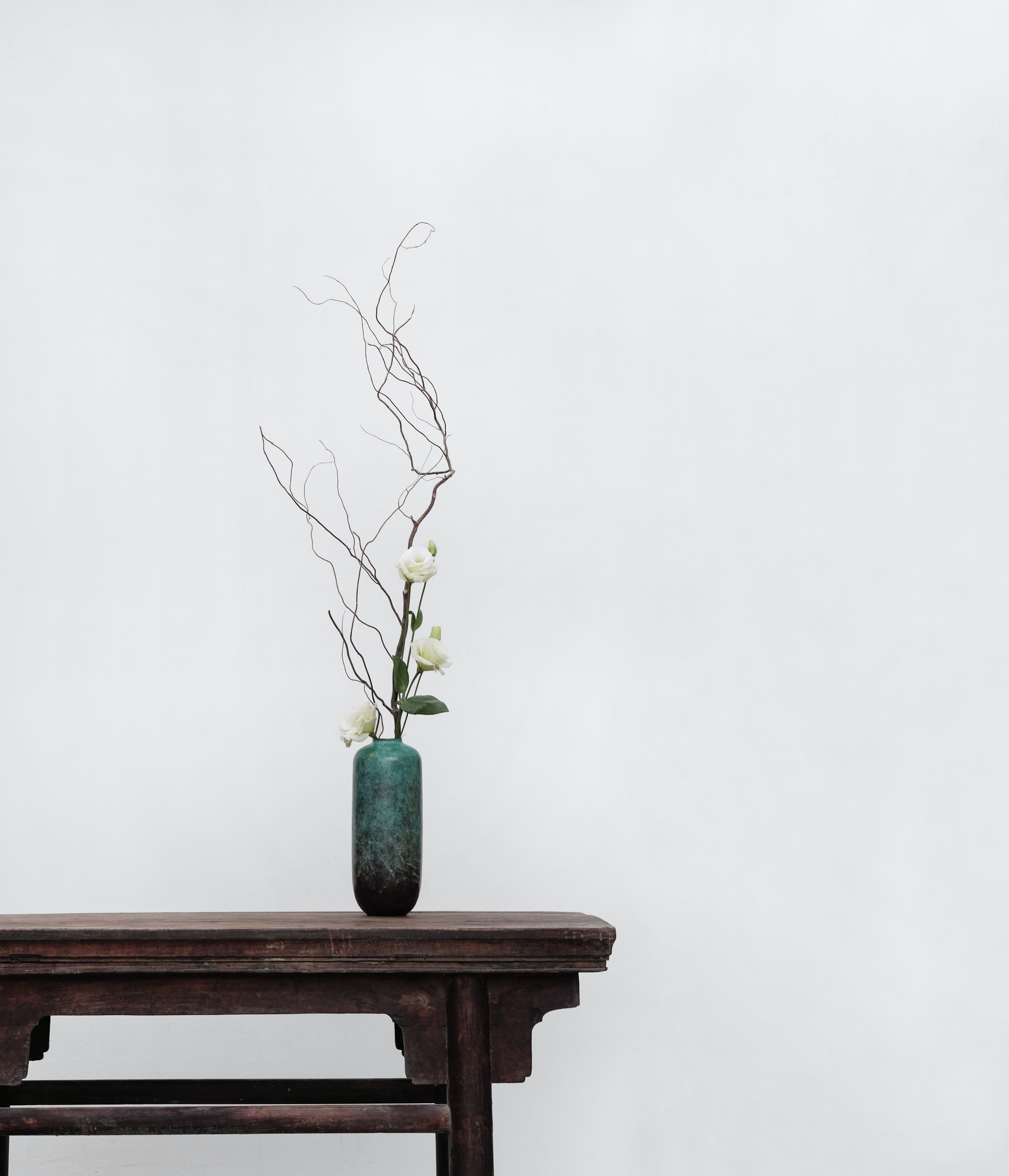 white flowers with green ceramic vase on top of brown wooden side table