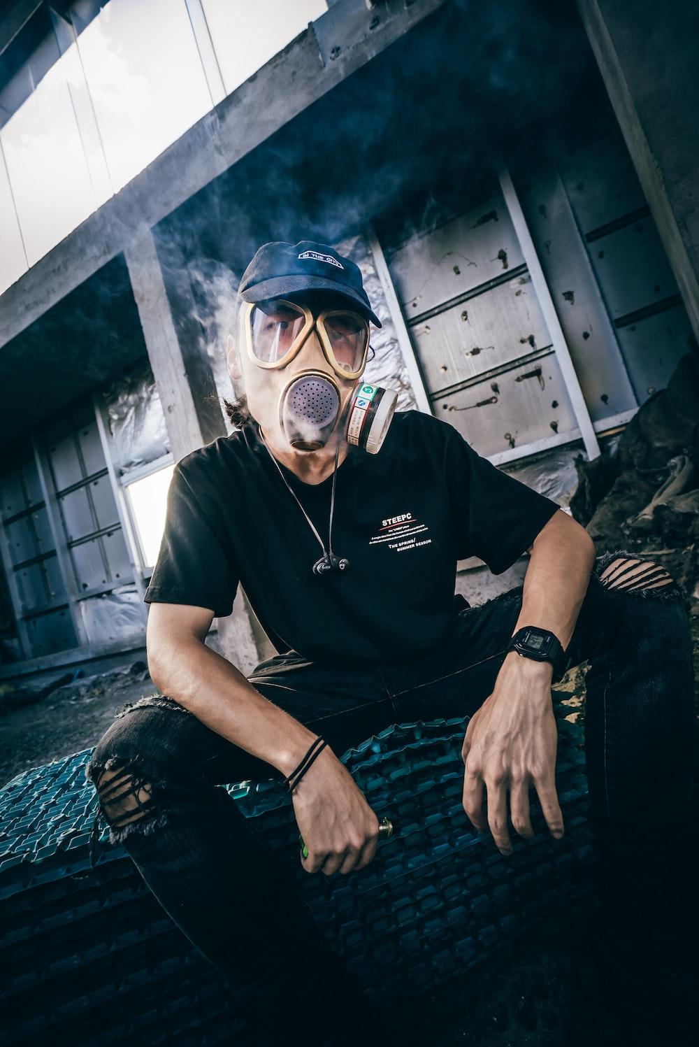 man wearing gas mask holding box mod