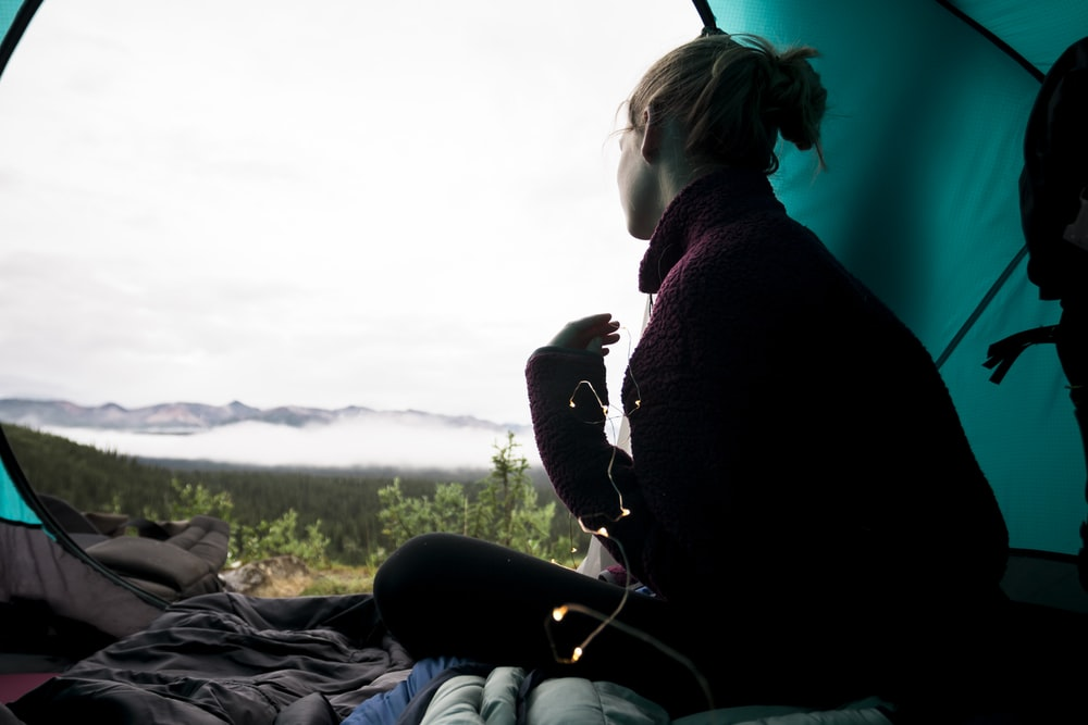 woman sitting inside teal camping tent during daytime