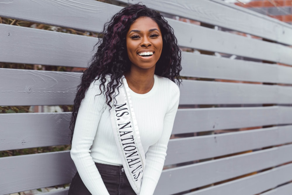 smiling woman wearing Ms. National U.S. sash leaning on pallet wall