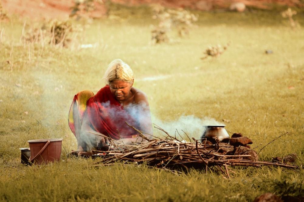 woman sitting near firewood