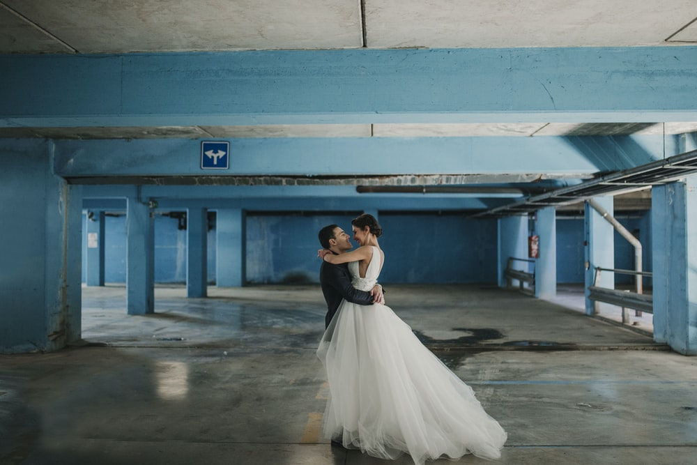 bride and groom hugging each other at parking space