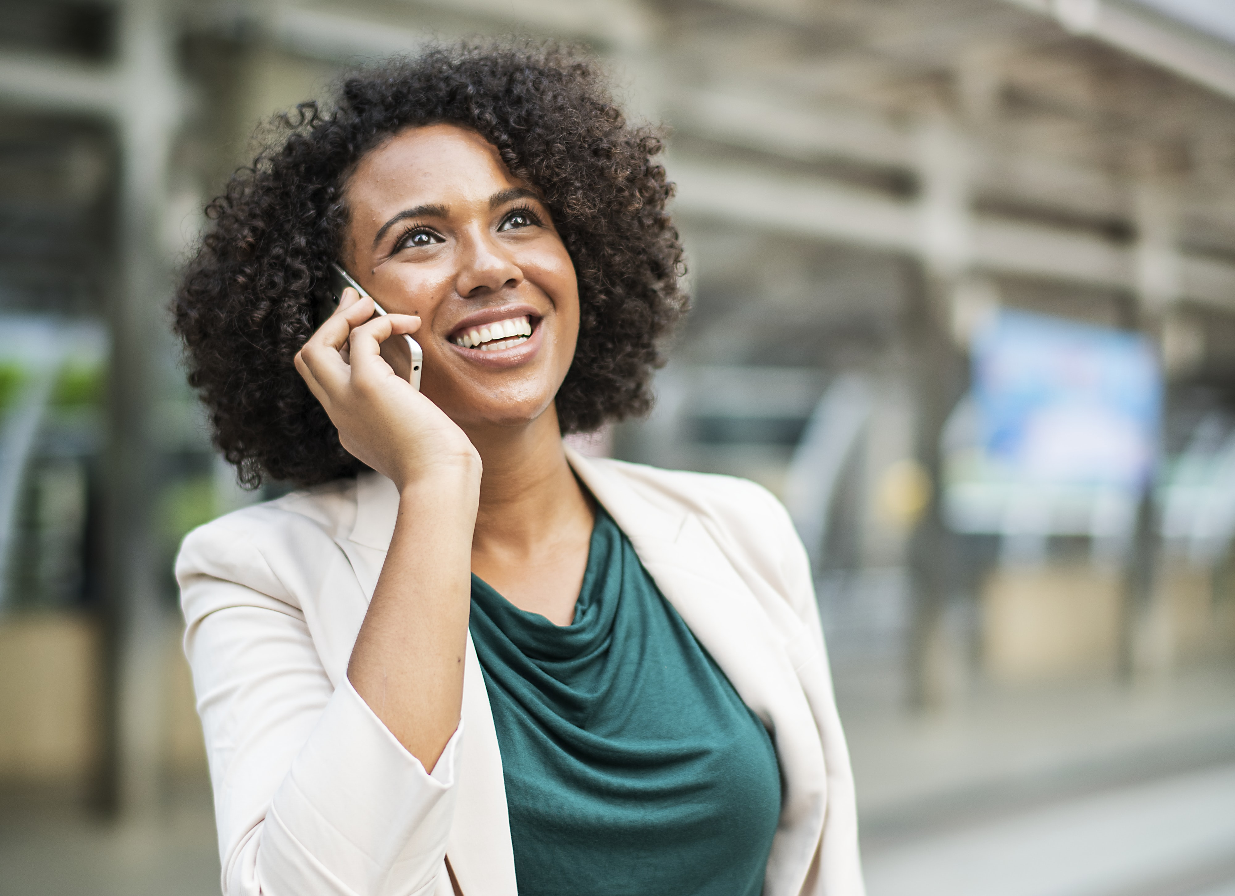 selective focus photography woman smiling while calling using smartphone