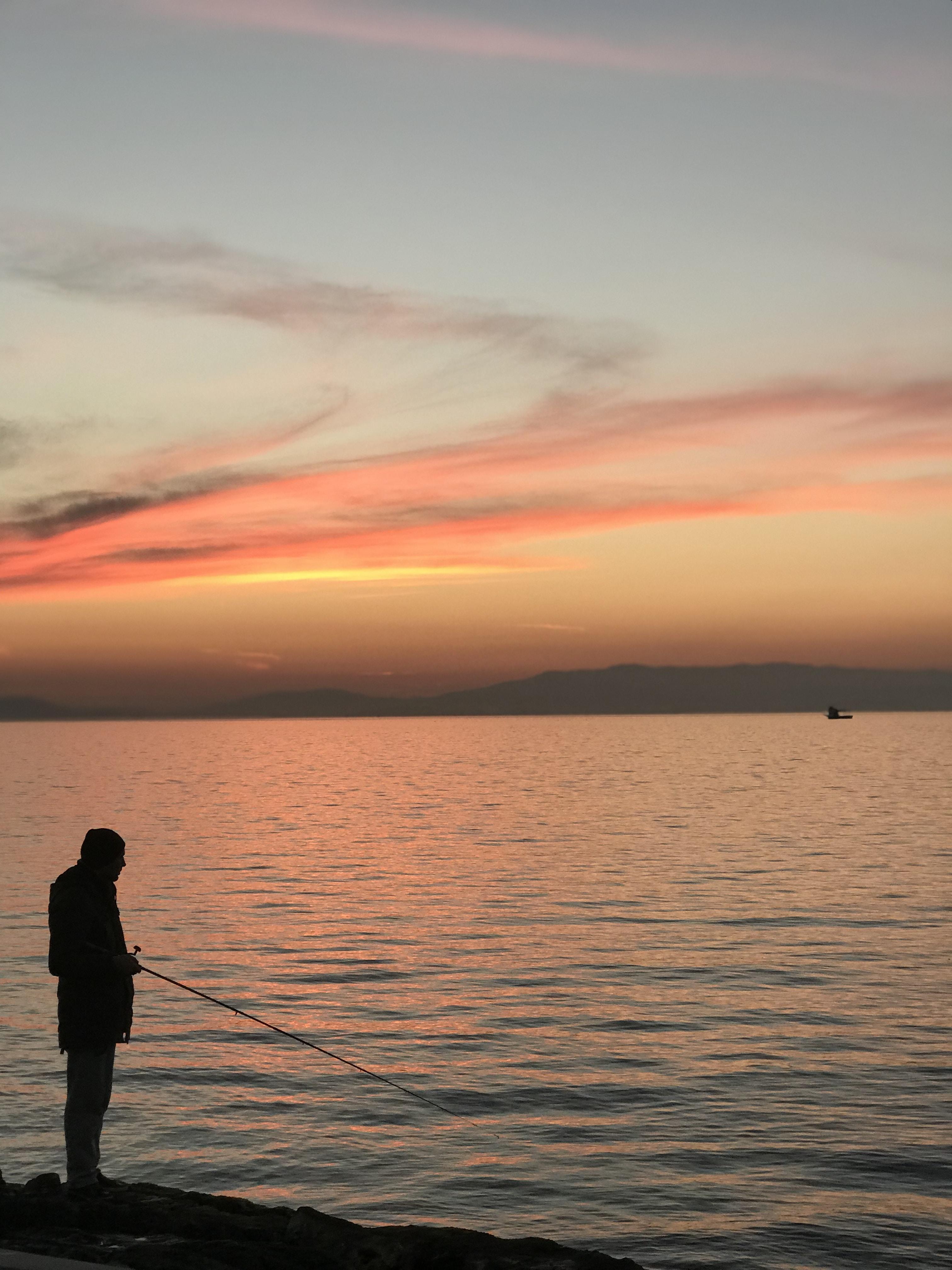man standing on edge fishing