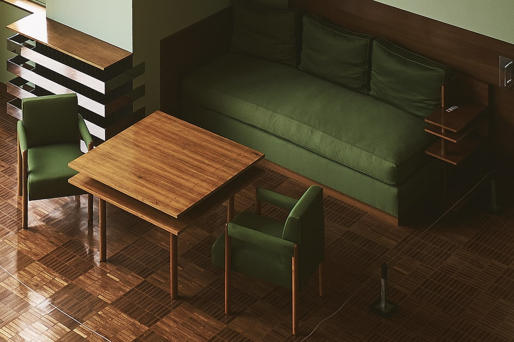 green leather sofa near wall in front of table