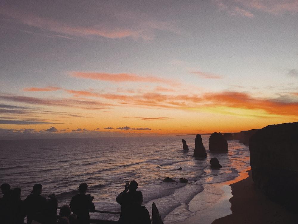 silhouette of people standing near 12 Apostles landmark in Australia