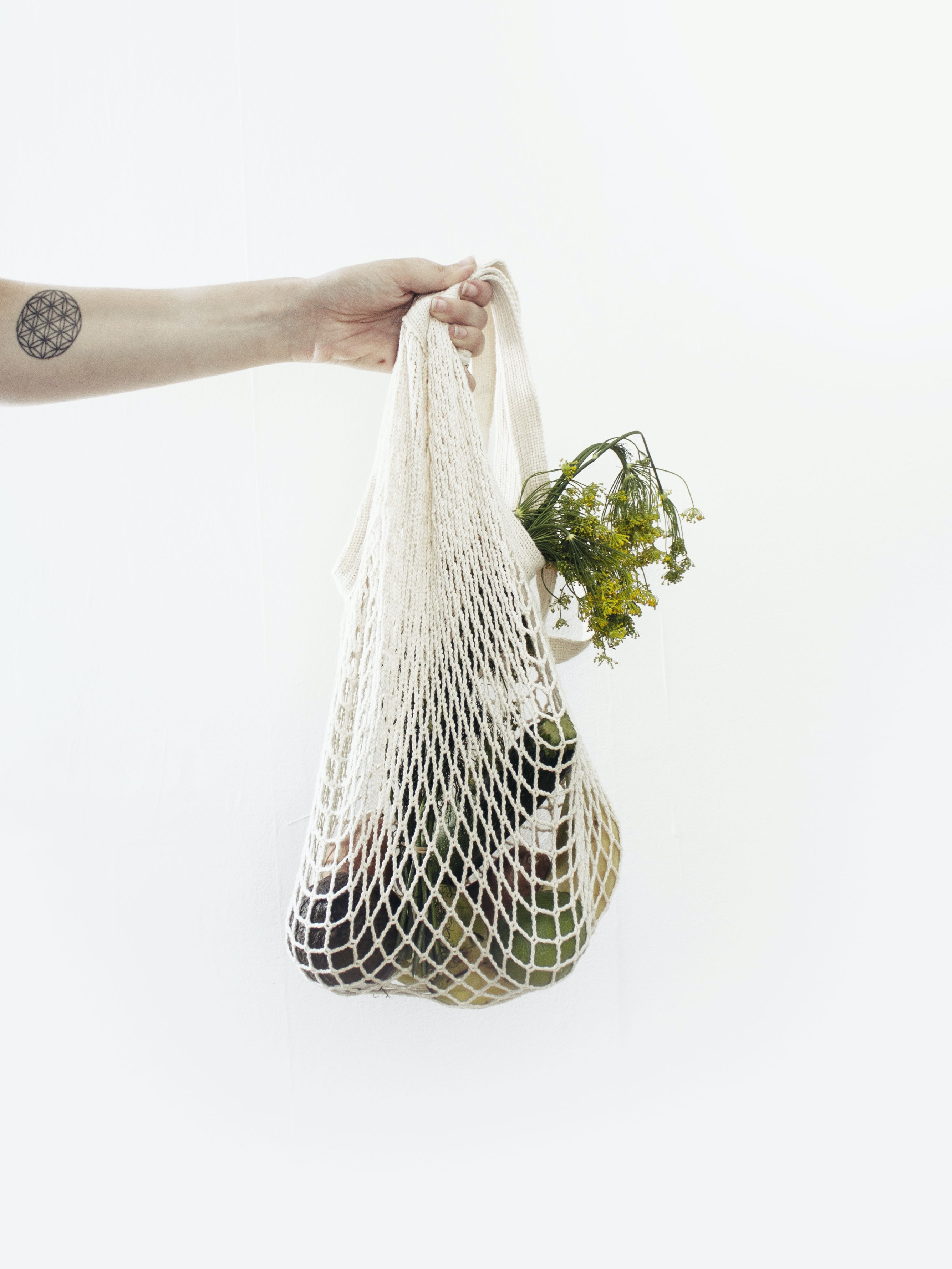 person holding white net with vegetable
