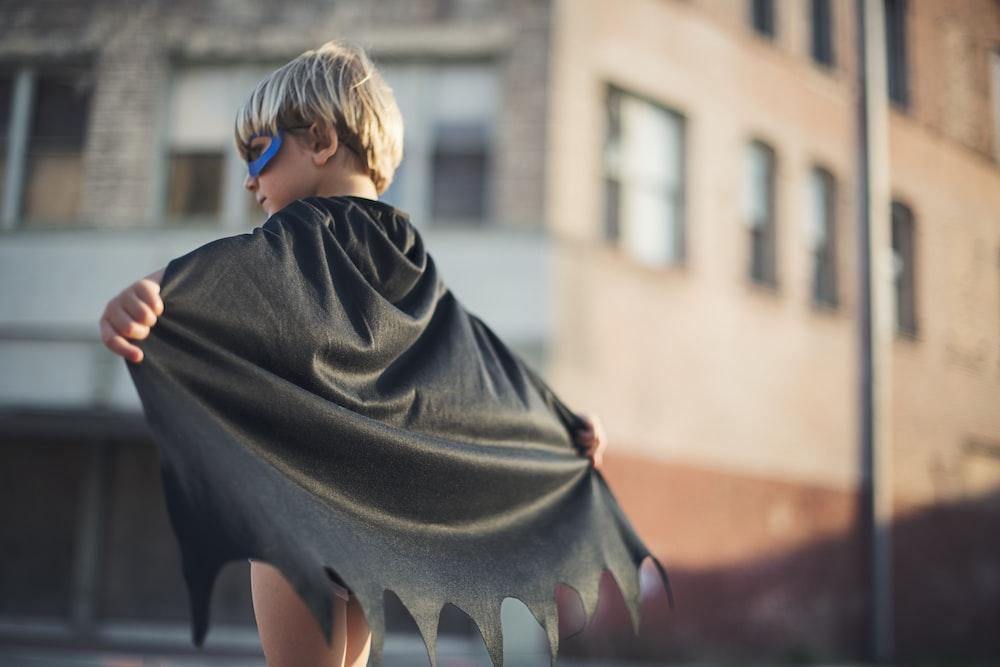 selective focus photography of boy wearing black Batman cape