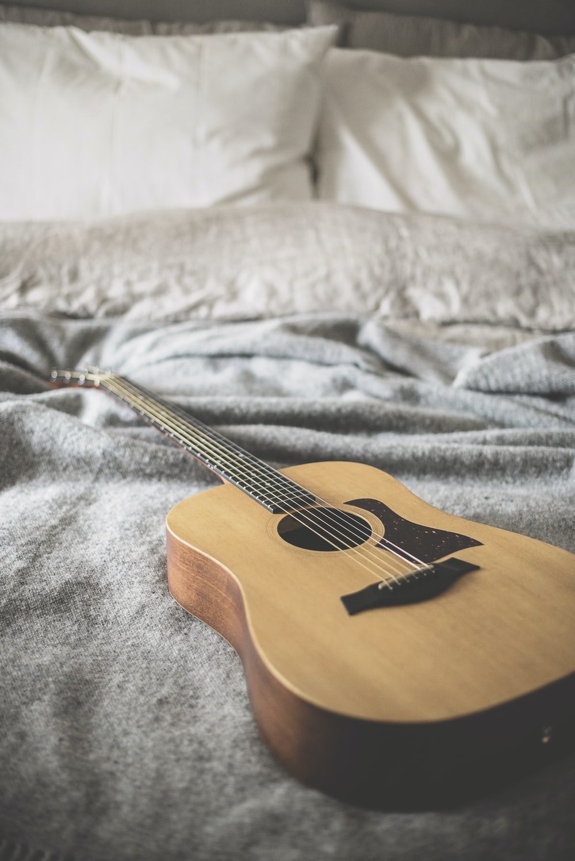brown acoustic guitar on gray blanket