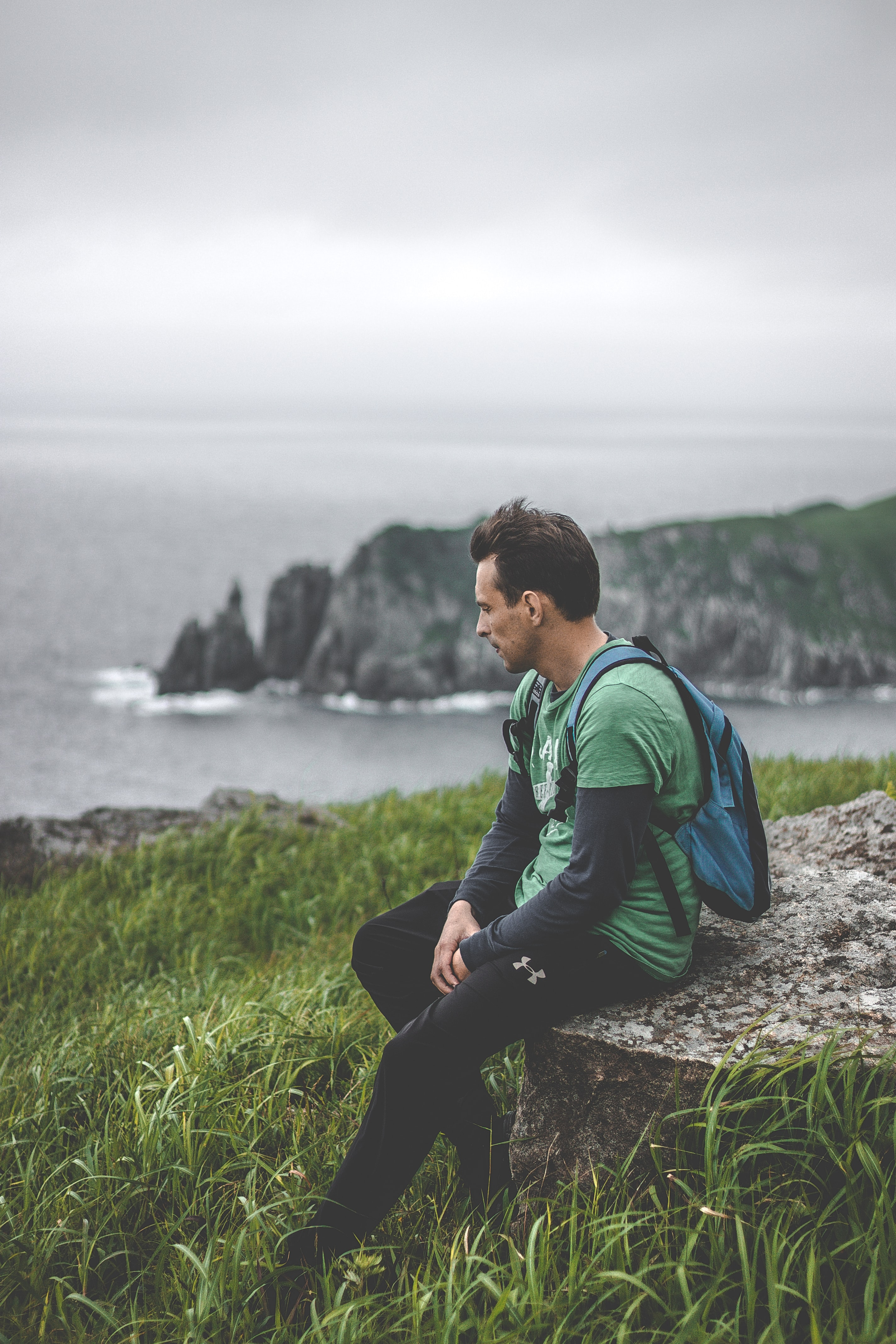 man sitting on gray rock with green grass