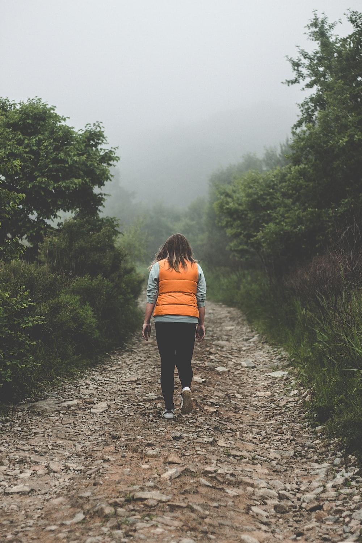 woman wearing orange life vest walking on pathway during daytime
