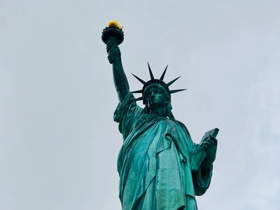 photo of statue of liberty during daytime neoclassical teams background