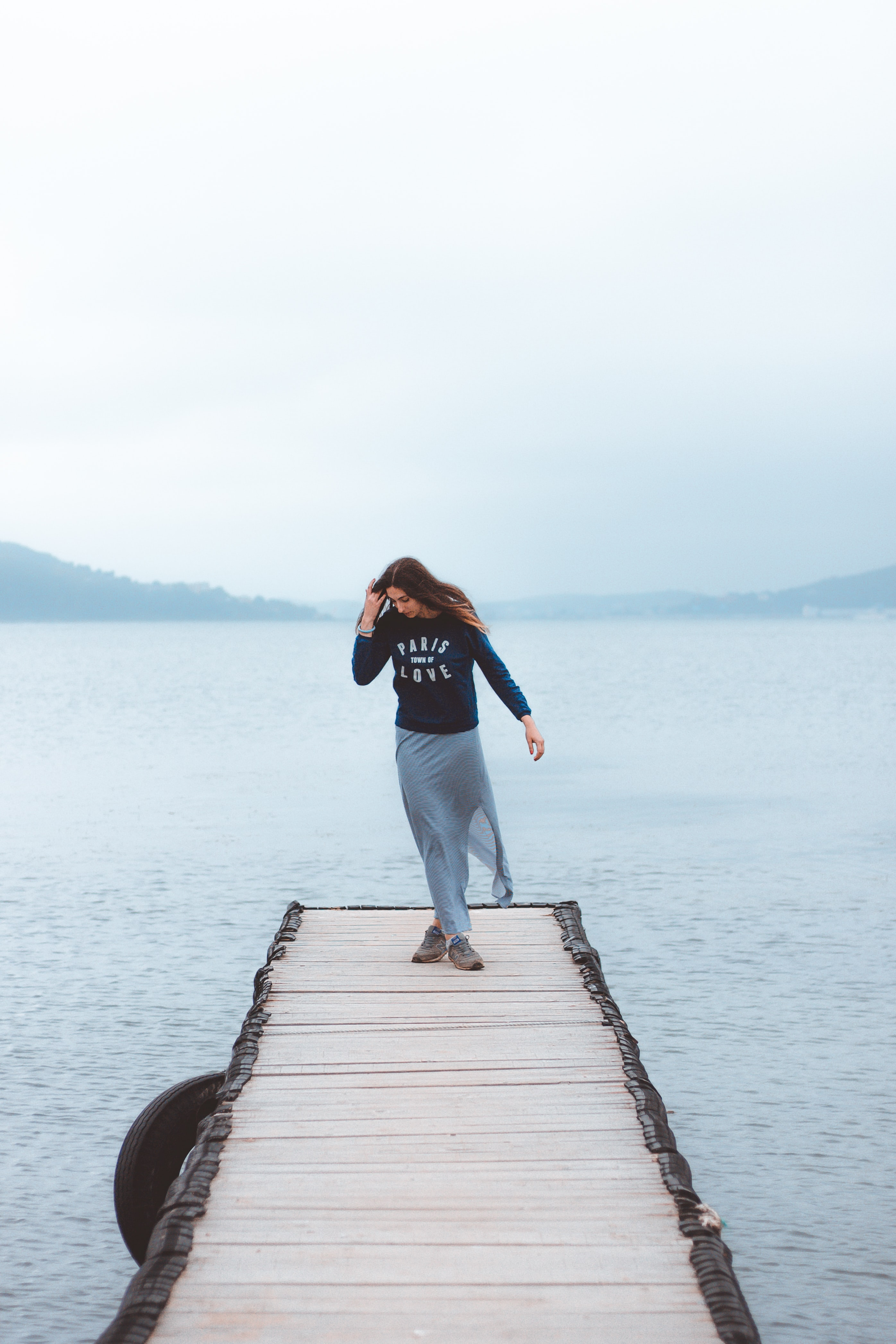 woman standing in the middle of wooden footbridge leading to the sea