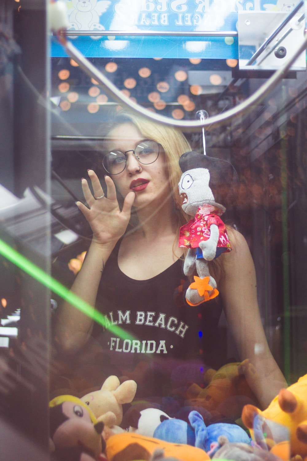 woman standing beside claw vending machine