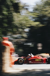 red and black Formula 1 racing car in time lapse photography